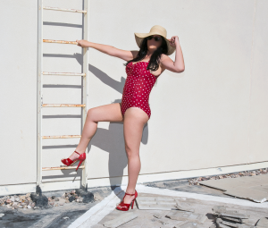 Kate Layne in red swimsuit on ladder